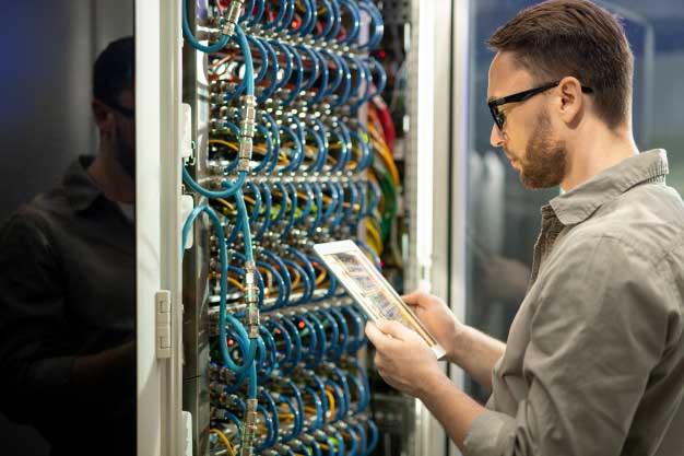 خدمات پشتیبانی شبکه حضوری کارشناس شبکه در حال بررسی چکلیست شبکه در اتاق سرور